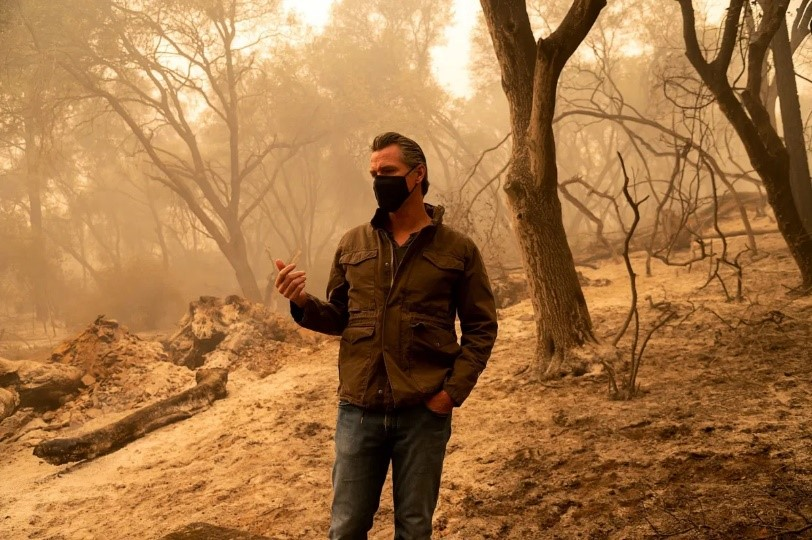 Governor Newsom stands wearing a mask with burned trees and charred ground behind him that is made hazy by smoke.