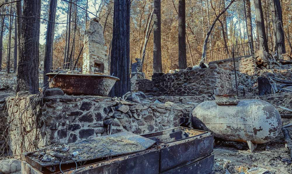 burned remnants of a home with burned trees in the background