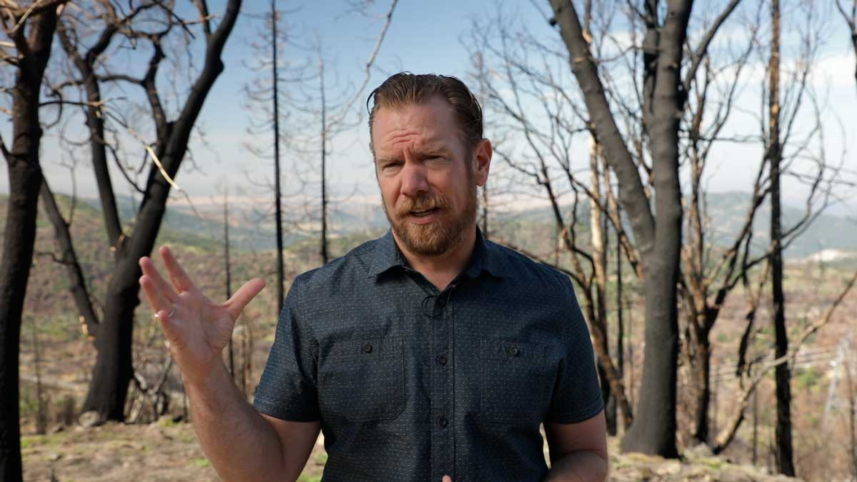 man talking in front of burned trees
