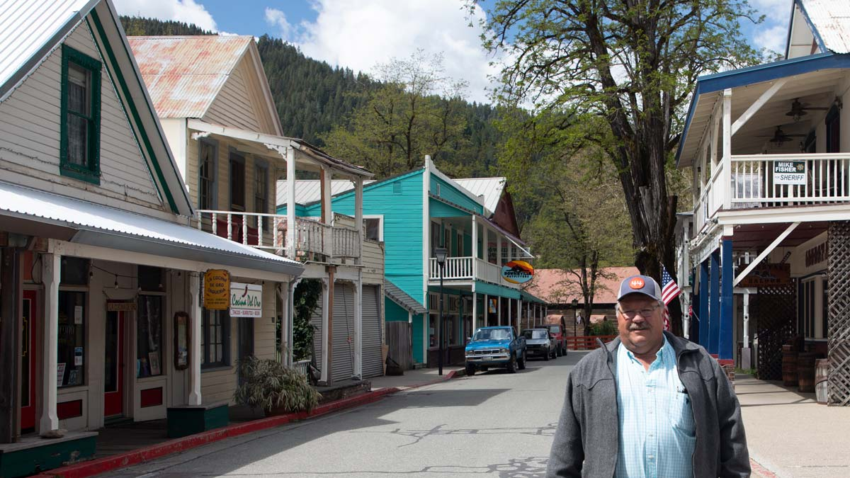 man standing in front of a street lines with gold rush era buildings and businesses
