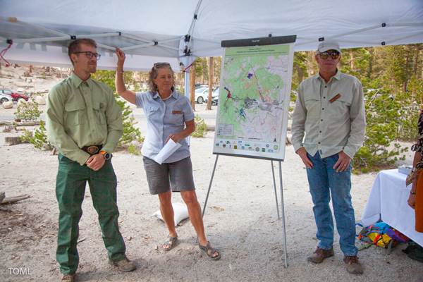 three people standing next to a map