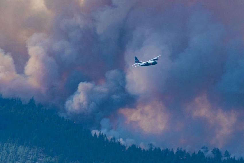 large smoke plume engulfs the sky above a forest with a small plane flying nearby